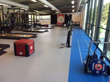 fitnes, tla v fitnesu, talna obloga pod telovadnimi napravami